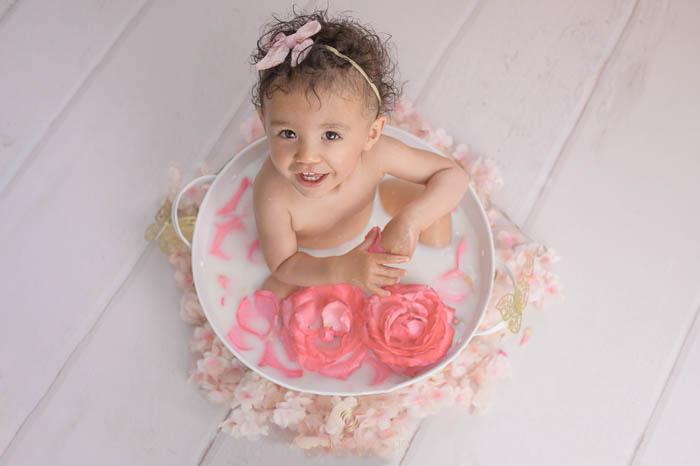 Photographe bébé à Tullins près de Voiron et Grenoble | Photo de bébé 1 an anniversaire, portrait d'une bébé fille qui mange des oranges dans son bain de lait