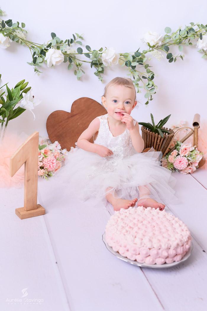 Photographe bébé à Tullins près de Voiron et Grenoble   Photo de bébé 1 an anniversaire, Smash the cake, bébé fille aux yeux bleus devant son gâteau en robe blanche sur fond blanc