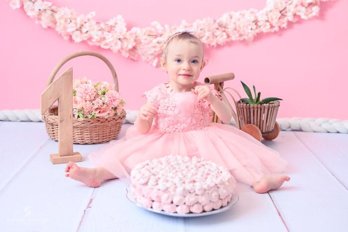 Photographe bébé à Tullins près de Voiron et Grenoble   Photo de bébé 1 an anniversaire, Smash the cake, bébé fille aux yeux bleus en robe rose devant son gâteau sur fond rose