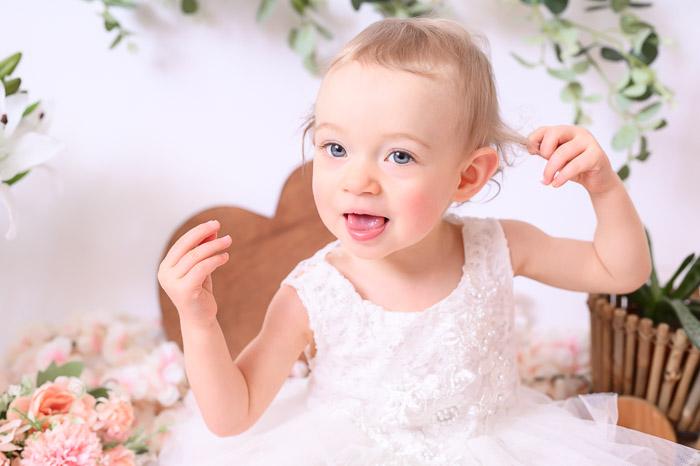 Photographe bébé à Tullins près de Voiron et Grenoble   Photo de bébé 1 an anniversaire, Smash the cake, bébé fille aux yeux bleus tire la langue sur fond blanc