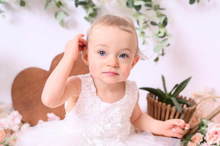 Photographe bébé à Tullins près de Voiron et Grenoble   Photo de bébé 1 an anniversaire, Smash the cake, bébé fille aux yeux bleus se tient les cheveux sur fond blanc