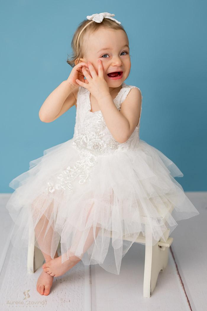 Photographe bébé à Tullins près de Voiron et Grenoble   Photo de bébé 1 an, bébé fille en robe blanche assise rigole sur fond bleu