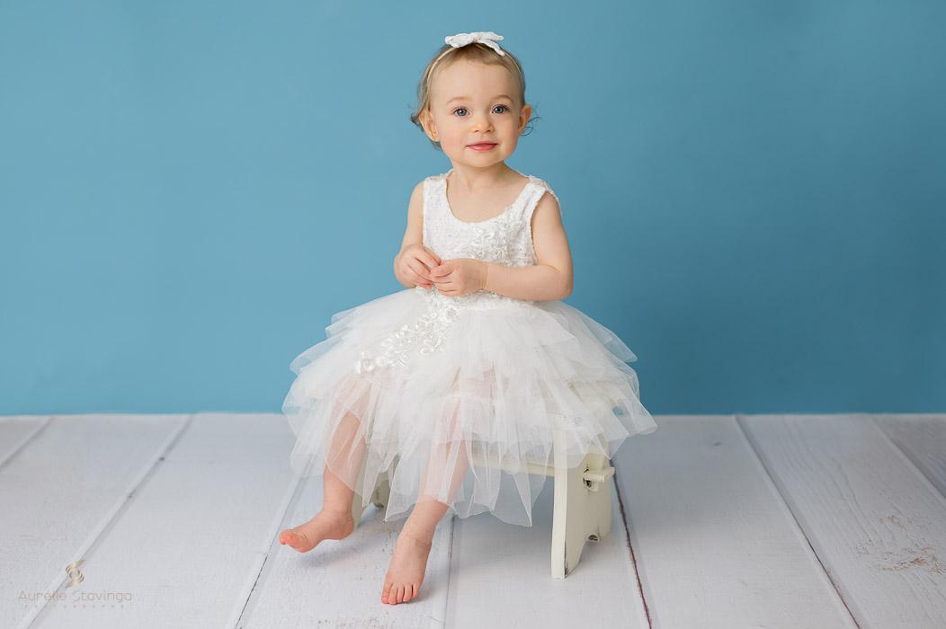 Photographe bébé à Tullins près de Voiron et Grenoble   Photo de bébé 1 an, bébé fille en robe blanche assise sur fond bleu