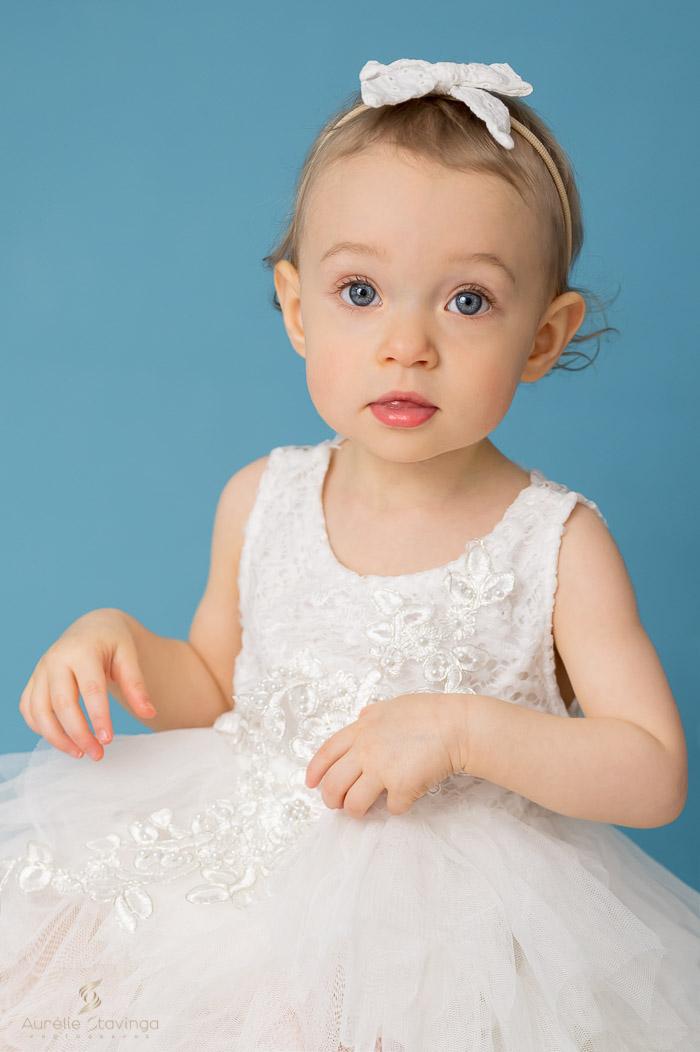 Photographe bébé à Tullins près de Voiron et Grenoble   Photo de bébé 1 an, bébé fille en robe blanche sur fond bleu
