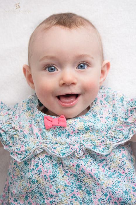 Photographe bébé à Tullins près de Voiron et Grenoble   Photo de bébé 3-6 mois, bébé fille au yeux bleus avec sourire en robe fleurie