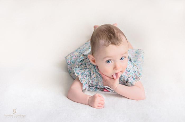 Photographe bébé à Tullins près de Voiron et Grenoble   Photo de bébé 3-6 mois sur fond beige, bébé fille sur le ventre au yeux bleus en robe fleurie qui tire la langue