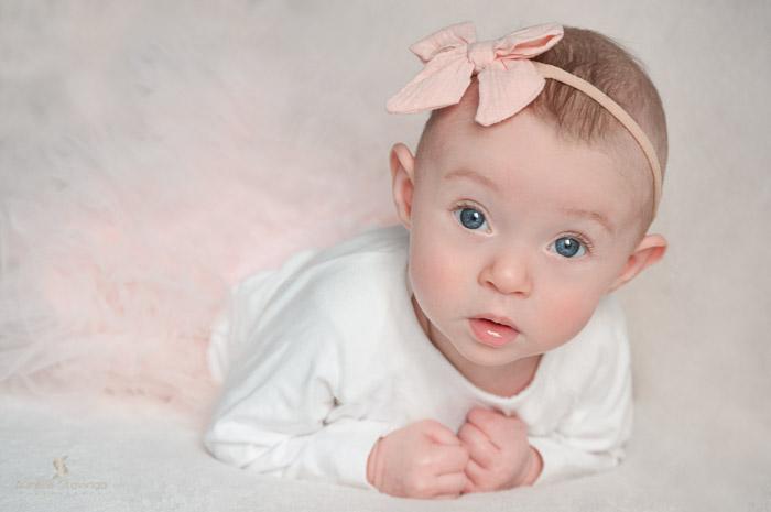 Photographe bébé à Tullins près de Voiron et Grenoble   Photo de bébé 3-6 mois, bébé fille au yeux bleus sur le ventre avec un grand regard et des yeux bleus