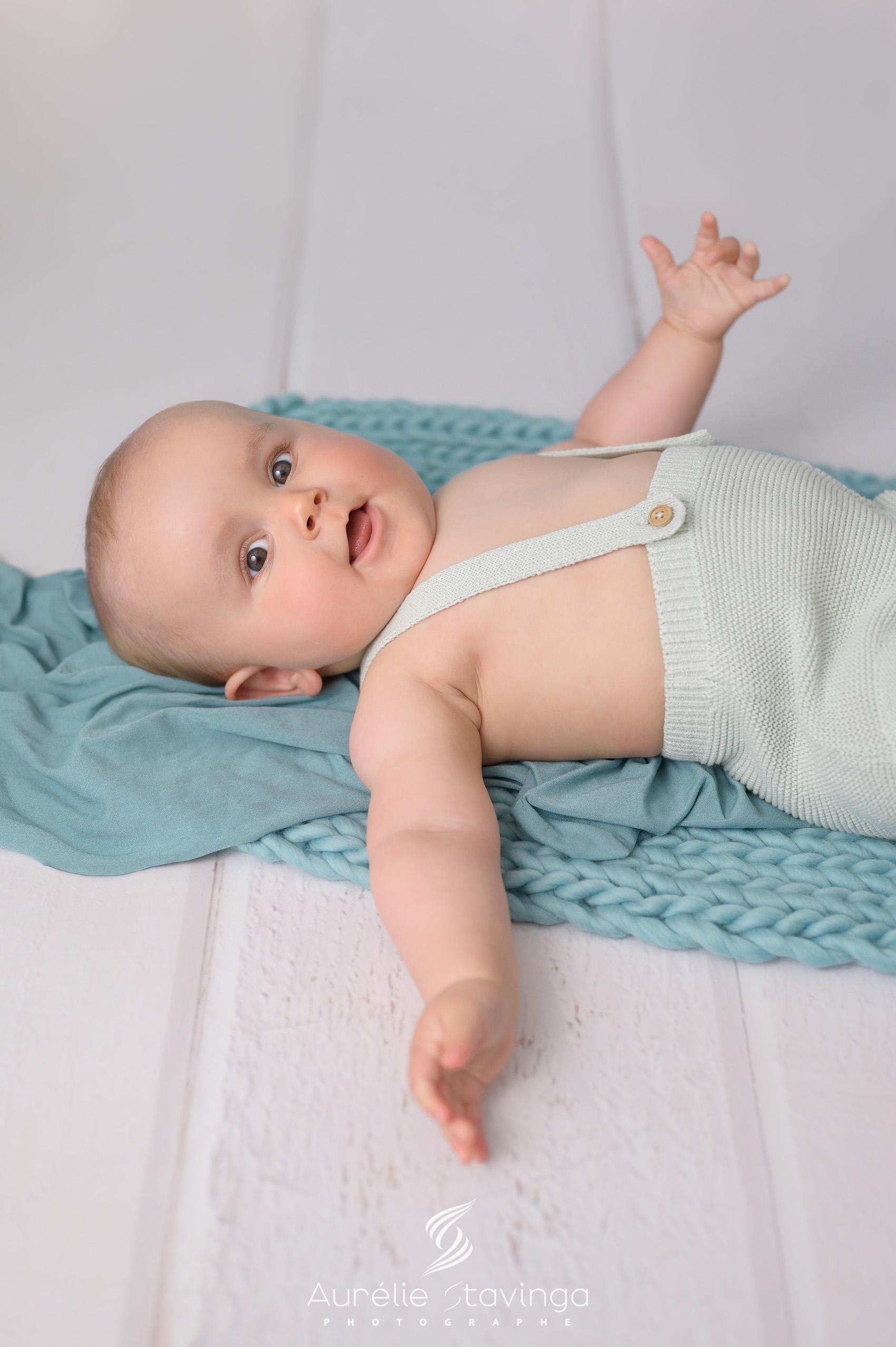 Photographe bébé à Tullins près de Voiron et Grenoble   Photo de bébé 3-6 mois, bébé fille au yeux bleus en robe bleue avec noeud dans les cheveux