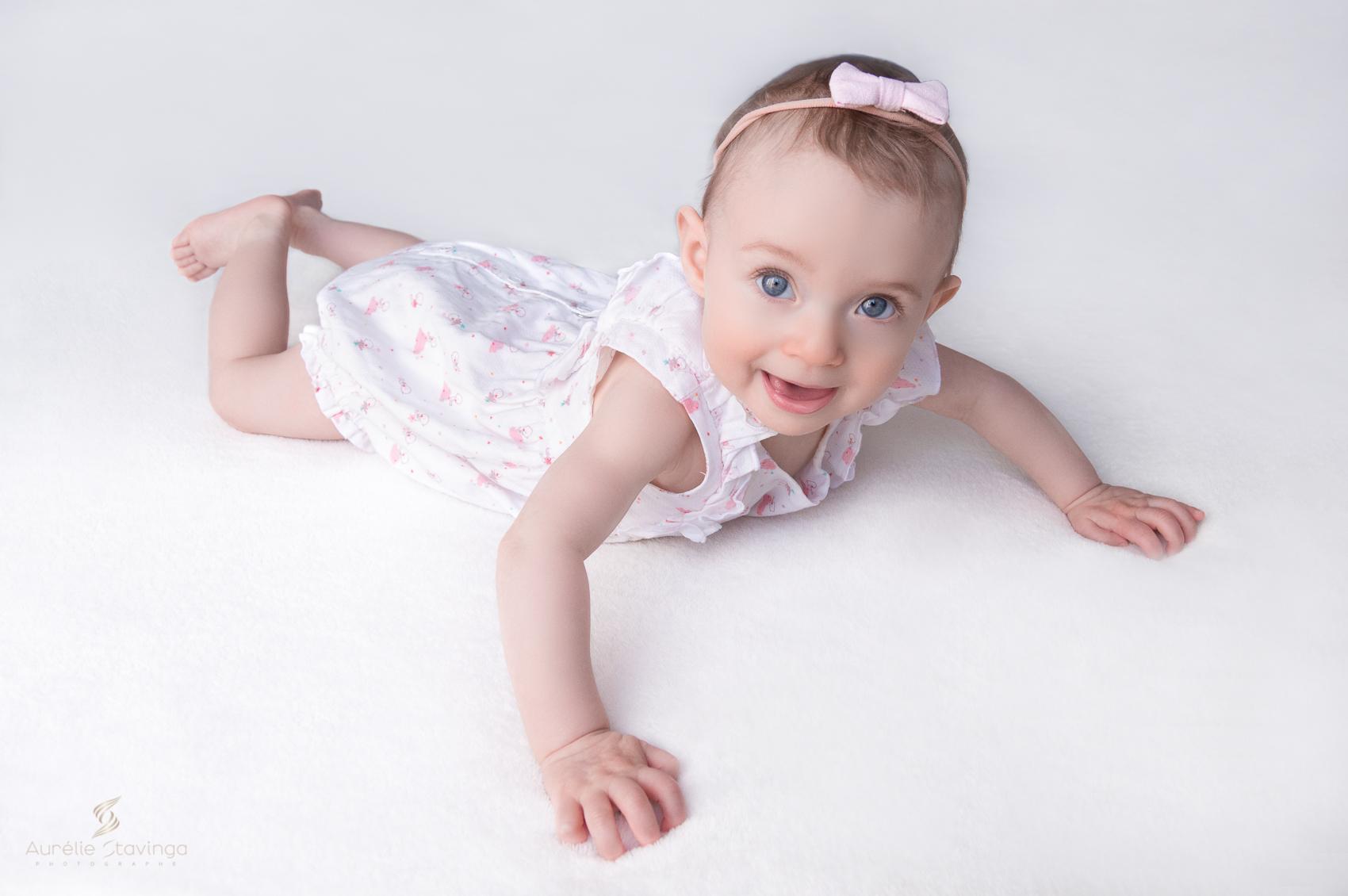 Photographe bébé à Tullins près de Voiron et Grenoble. Bébé fille au yeux bleus avec grand sourire, sur le ventre et sur fond rose