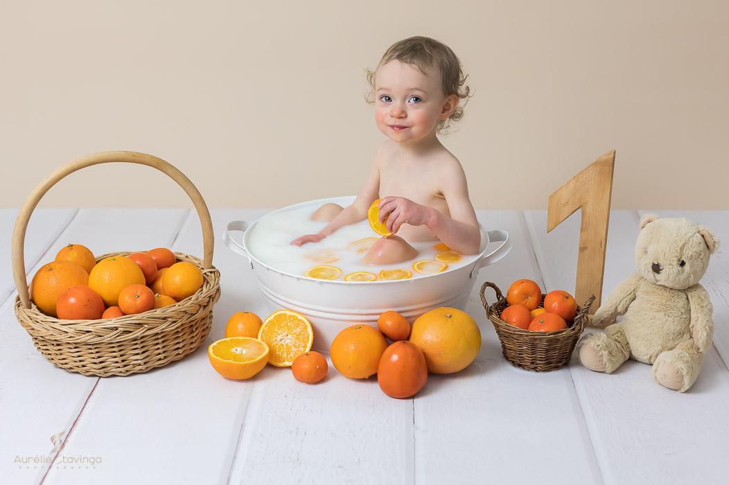 Photographe bébé à Tullins près de Voiron et Grenoble | Photo de bébé 8-10 mois, bébé fille de 1 an qui joue avec une tranche d'orange dans son bain de lait