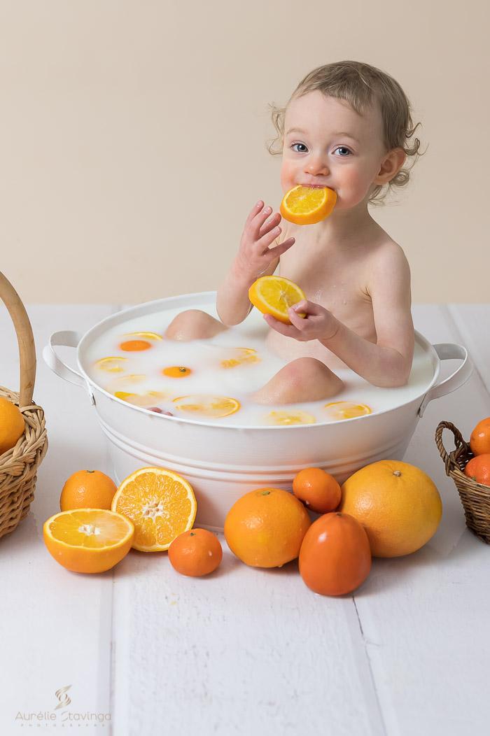Photographe bébé à Tullins près de Voiron et Grenoble | Photo de bébé 8-10 mois, bébé fille qui joue avec une tranche d'orange dans son bain de lait