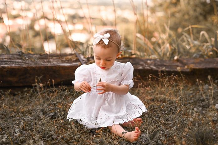 Photographe bébé à Tullins près de Voiron et Grenoble | Photo de bébé 8-10 mois, bébé fille en robe blanche qui joue dans l'herbe à l'extérieur