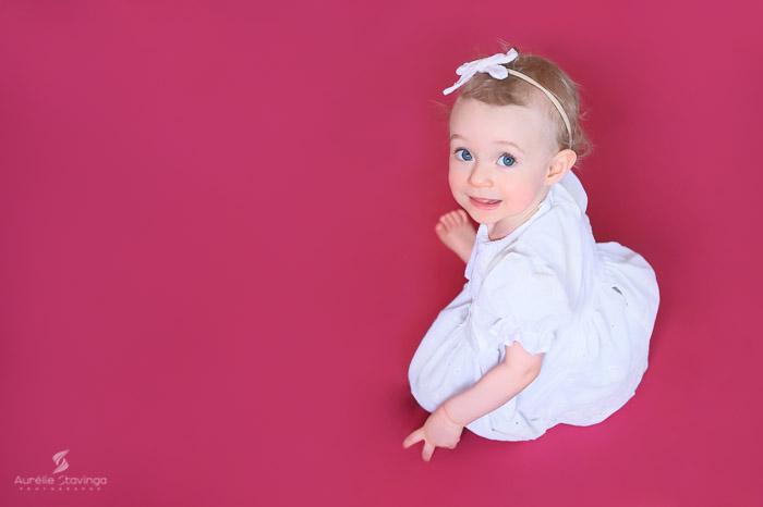 Photographe bébé à Tullins près de Voiron et Grenoble | Photo de bébé 8-10 mois, bébé fille au yeux bleus assise en robe blanche