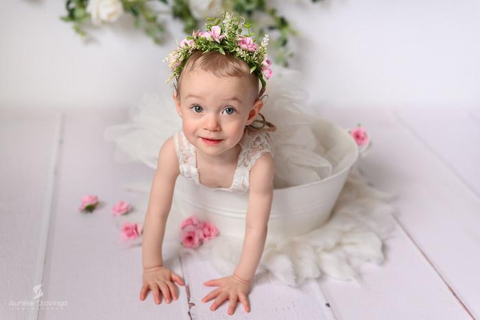 Photographe bébé à Tullins près de Voiron et Grenoble. Bébé fille à quatre patte robe blanche et fleurs roses