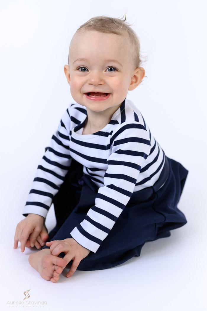 Photographe bébé à Tullins près de Voiron et Grenoble | Photo de bébé 8-10 mois, bébé fille en robe bleu marine assise qui tient ses pieds et fait un grand sourire