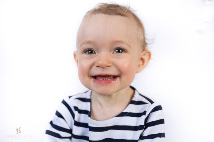 Photographe bébé à Tullins près de Voiron et Grenoble | Photo de bébé 8-10 mois, bébé fille en bleu marine avec un grand sourire et beau regard