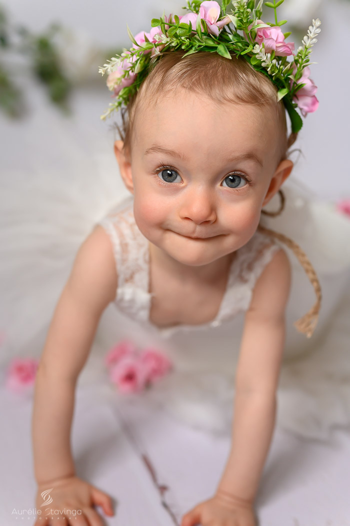 Photographe bébé à Tullins près de Voiron et Grenoble | Photo de bébé 8-10 mois, bébé fille au yeux bleus avec une couronne de fleurs à quatre pattes