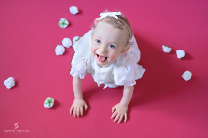 Photographe bébé à Tullins près de Voiron et Grenoble | Photo de bébé 8-10 mois, bébé fille au yeux bleus à quatre pattes qui tire la langue en robe blanche sur fond rose et fleurs blanches