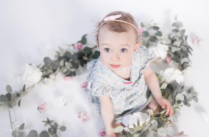 Photographe bébé à Tullins près de Voiron et Grenoble | Photo de bébé 8-10 mois, bébé fille en robe fleurie aux yeux bleus et grand regard