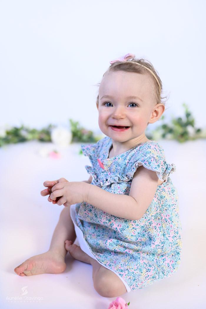 Photographe bébé à Tullins près de Voiron et Grenoble | Photo de bébé 8-10 mois, bébé fille en robe fleurie au yeux bleus et qui sourit