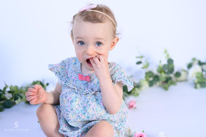 Photographe bébé à Tullins près de Voiron et Grenoble | Photo de bébé 8-10 mois, bébé fille au yeux bleus assise avec robe fleurie