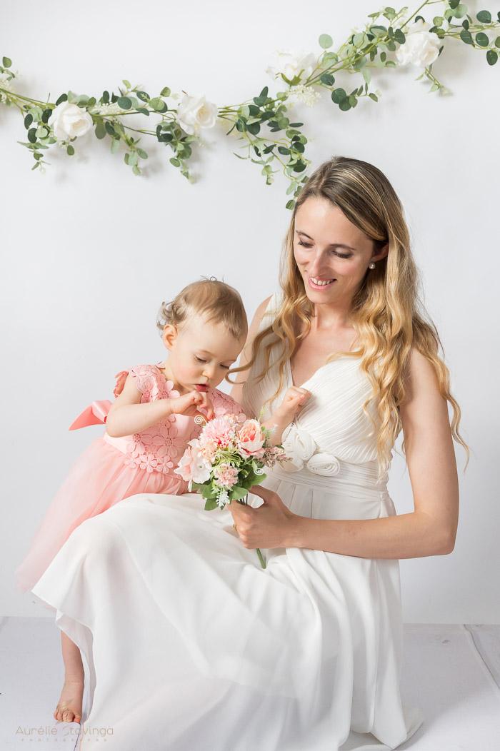Photographe bébé et maman à Tullins près de Voiron et Grenoble | Photo de bébé et maman, avec maman sur un genou en robe blanche tenant un bouquet de fleurs avec lequel sa fille debout en robe rose joue