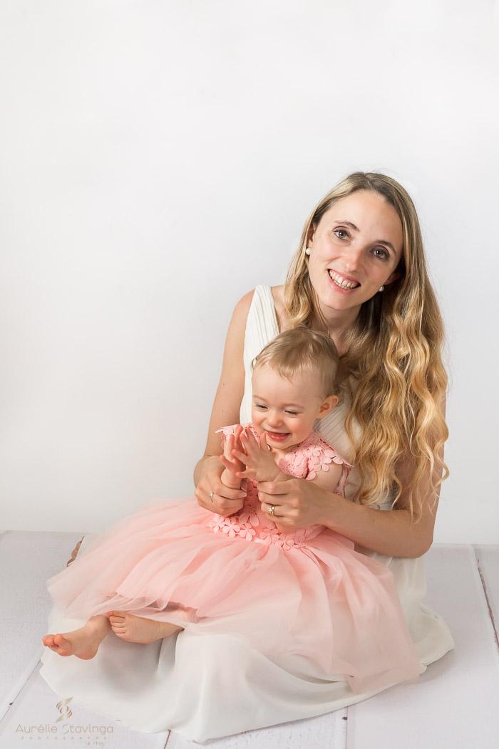 Photographe bébé et maman à Tullins près de Voiron et Grenoble | Photo de bébé et maman, avec maman assise en robe blanche et sa fille sur les genoux en robe rose, qui joue avec les mains de sa mamanc