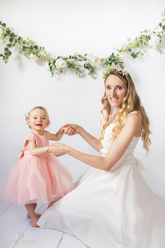 Photographe bébé et maman à Tullins près de Voiron et Grenoble | Photo de bébé et maman se tenant les mains, avec maman assise en robe blanche et bébé debout en robe rose, toutes les deux souriantes