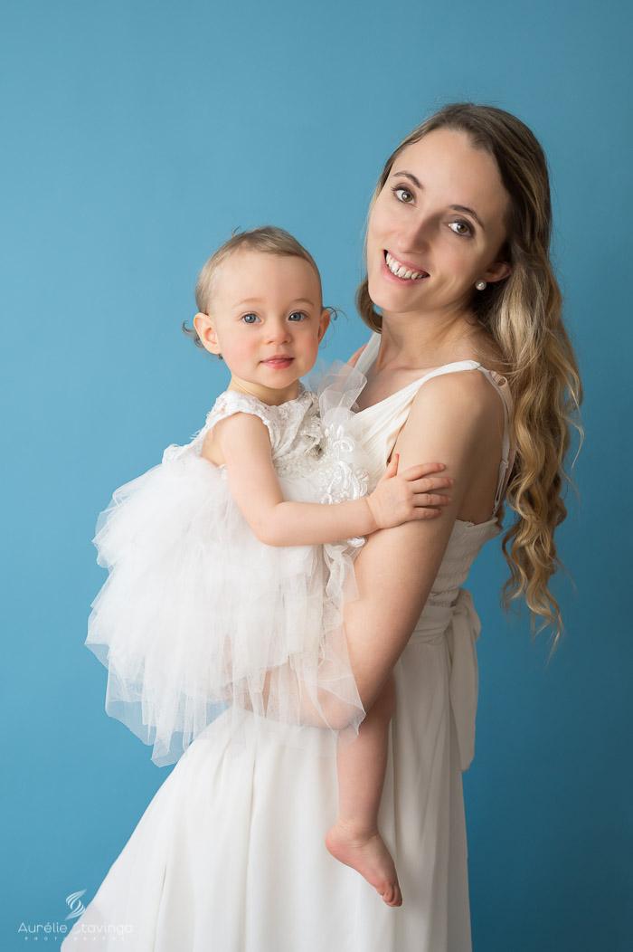 Photographe bébé et maman à Tullins près de Voiron et Grenoble | Photo de bébé et maman, avec maman souriante tenant son enfant dans ses bras sur fond bleu