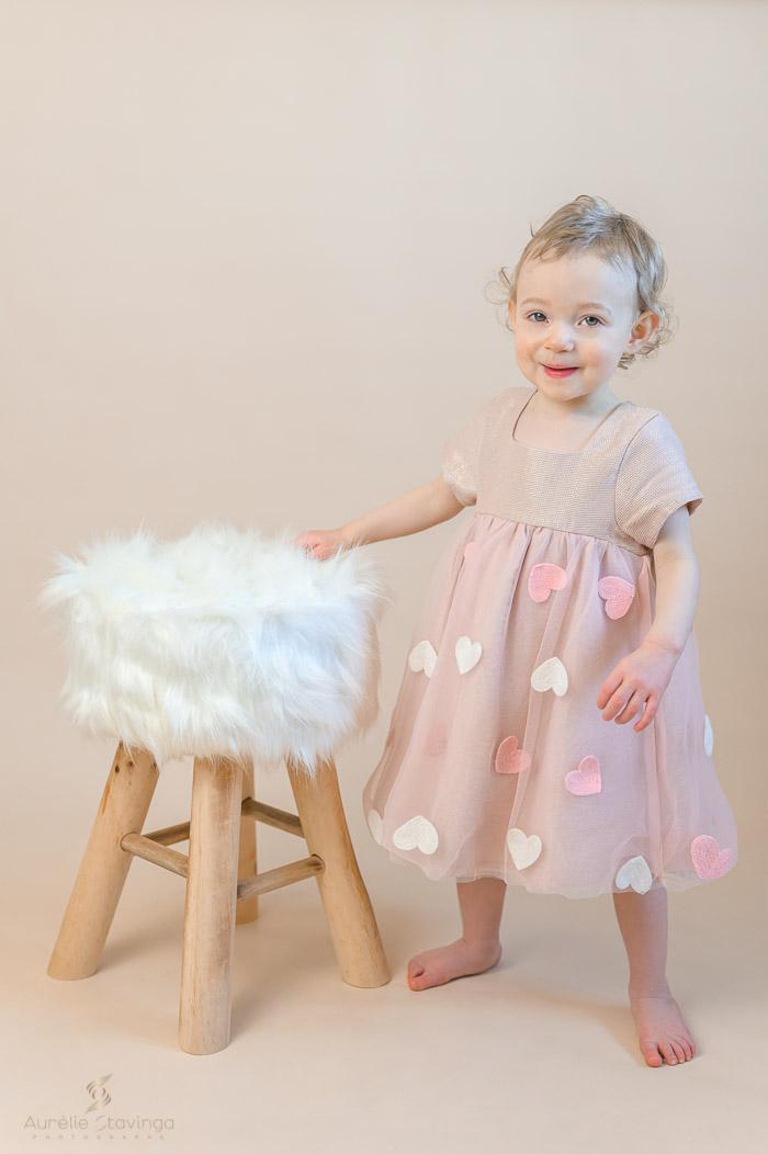 Photographe portrait enfant à Tullins près de Voiron et Grenoble | Photo portrait d'enfant fille souriante en robe crème debout la main sur le tabouret