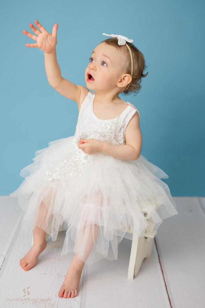 Photographe portrait enfant à Tullins près de Voiron et Grenoble | Photo portrait d'enfant fille levant la main en robe blanche sur fond bleu assise sur un banc