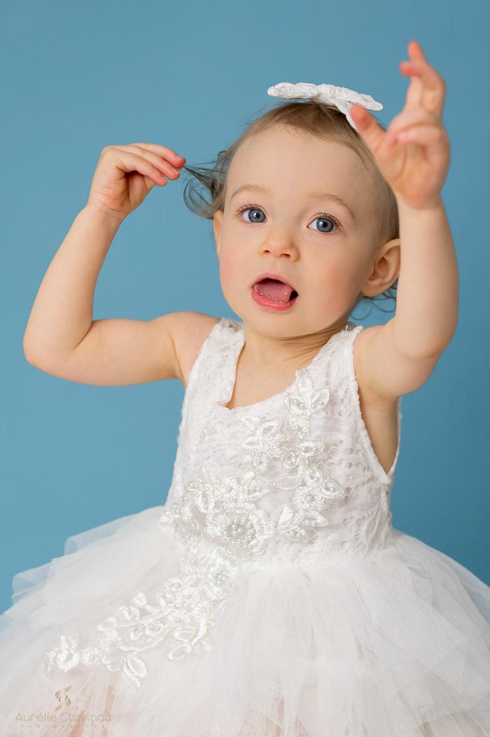 Photographe portrait enfant à Tullins près de Voiron et Grenoble | Photo portrait d'enfant fille qui joue avec ses cheveux sur fond bleu