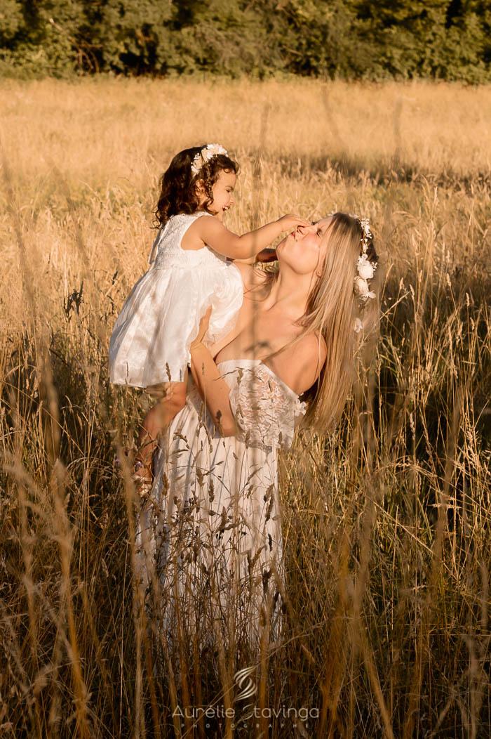 Photographe de famille à Tullins près de Voiron et Grenoble | Photo portrait de famille sur fond bleu avec maman souriante qui a dans ses bras sa fille bébé. Elles portent toutes les deux une robe blanche.