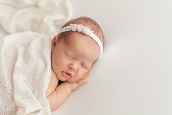 Photographe de naissance à Tullins près de Voiron et Grenoble   Photo de naissance sur fond crème, bébé fille qui dort paisiblement avec un bandeau de fleurs crème